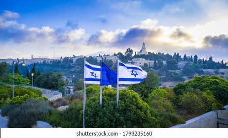 Israeli flags with beautiful sunrise view of Mount Zion: Dormition Abbey, Jerusalem university college and greek ceminary; with walls of Jerusalem's Old City, leading up to the Tower of David