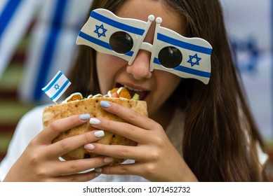 Israeli girl holding pita with falafel and a flag on Israel's Independence Day