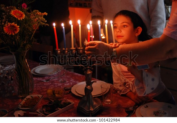 Israeli Jewish family lighting all menorah candles on the 8th day of the Jewish holiday of Hanukkah.Real people. Copy space