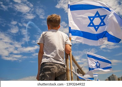 Israeli kid watching the aviation show on the 71 Israel Independence Day with a flag of Israel against the blue sky.