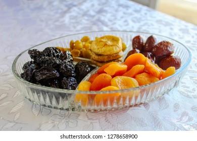 Israeli mix of dried fruits - symbols of Jewish holiday Tu Bishvat. Apricots, Dates, Raisins, Prunes, Figs in a glass tray