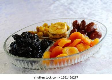 Israeli mix of dried fruits - symbols of Jewish holiday Tu Bishvat. Dates, Apricots, Raisins, Prunes, Figs in a glass tray