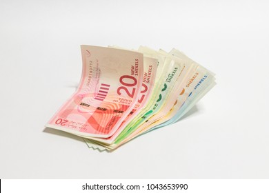 Israeli money stack of new Israeli banknotes of different value in shekels (NIS) isolated on a white background