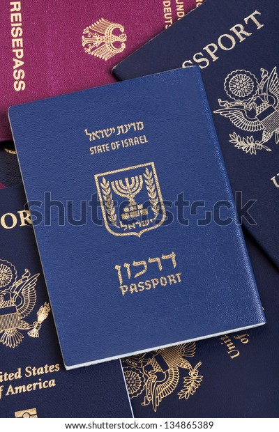 An Israeli passport resting on a stack of American and German passports.