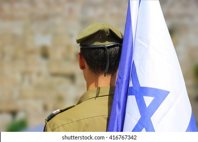 Israeli soldier with flag of Israel on blurred background of Western Wall