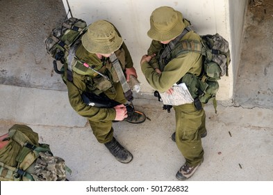 Israeli soldiers holding maps. Israeli soldiers preparing for a raid. Israeli soldiers in urban warfare training. Israeli soldiers in a military training base. Officers waiting for orders.