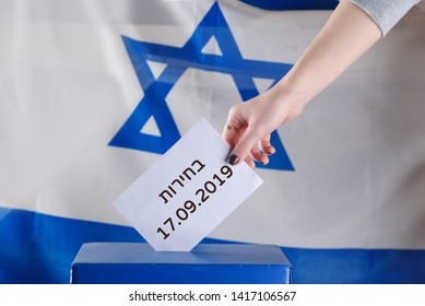 Israeli woman votes on election day. Close up of hand. Hebrew text Elections 17.09.2019 on Israel flag background. Israel to hold new elections 17 September 2019 after ruling coalition talks fail.