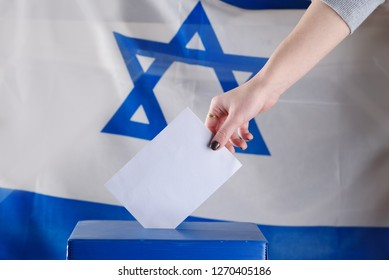 Israeli woman votes at a polling station on election day.Close up of hand with votes paper on Israel flag background. Israeli legislative Elections for the 21st Knesset Israel 9 April 2019