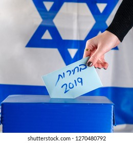 Israeli woman votes at a polling station on election day.Close up of hand. Hebrew text Elections 2019 on Israel flag background. Israeli legislative Elections for the 21st Knesset Israel 9 April 2019