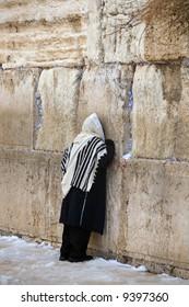 Israelite being prayed in western wall in Jerusalem in winter in snow.