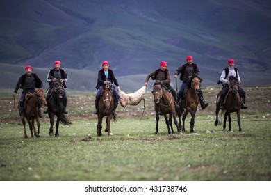 ISSYK KUL, KYRGYZSTAN: MAY 28, 2016: Nomadic horse riders hold the goat carcass, at the horse games in Issyk Kul Lake, Kyrgyzstan.