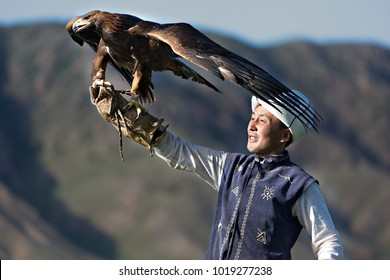 ISSYK KUL, KYRGYZSTAN - MAY 29, 2017: Golden eagle trainer holds his eagle during eagle hunter games in Issuk Kul Lake, Kyrgyzstan.