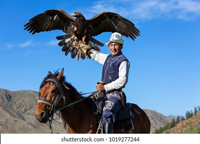 ISSYK KUL, KYRGYZSTAN - MAY 29, 2017: Golden eagle trainer holds his eagle during eagle hunter games in Issyk Kul Lake, Kyrgyzstan.