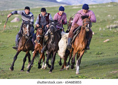 ISSYK KUL, KYRGYZSTAN - MAY 29, 2017: Nomadic horse riders try to grab goat carcass from each other, during traditional horse games known as Buzkashi or Kok Par, in Issyk Kul, Kyrgyzstan.