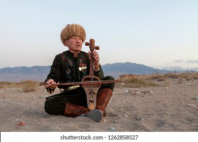 ISSYK KUL, KYRGYZSTAN - OCTOBER 15, 2017: Kyrgyz musician plays traditional musical instrument known as Kyl Kiak, in Issyik Kul, Kyrgyzstan