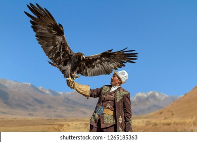 ISSYK KUL, KYRGYZSTAN - OCTOBER 16, 2017: Eagle hunter and his Golden Eagle with wings wide spread, in Issyk Kul, Kyrgyzstan
