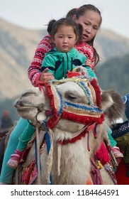 Issyk Kul, Kyrgyzstan-September 4, 2018: Kyrgyz nomad girls riding a Bactrian Camel at the World Nomad Games