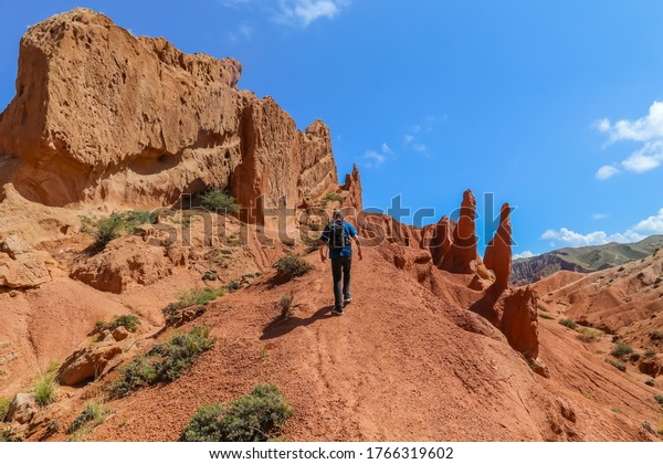 Issyk-Kul, Kyrgyzstan - August 19,2018: Hiker on the red sandstone rock formations Seven bulls and Broken heart, Jeti Oguz canyon in Kyrgyzstan, Issyk-Kul region, Central Asia