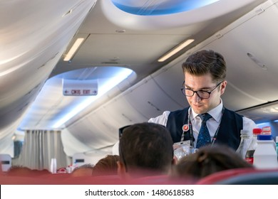 Istambul, Turkey - July 27, 2019: A young male flight attendant serving drinks to a passenger onboard a economy class cabin.