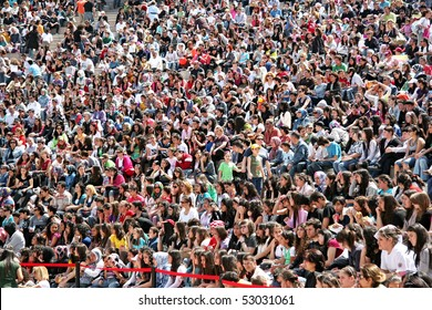 """ISTANBUL - APRIL 25: Crowd of people watch as the dance performance in """"National Sovereignty and Children Day"""" festival at Maltepe University on April 25, 2010 in Istanbul, Turkey."""