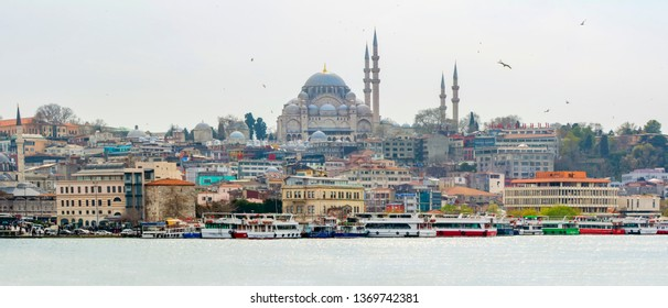 Istanbul, Turkey– April 6 , 2019: View touristic landmarks from sea voyage on Bosphorus. Cityscape of Istanbul at sunset - old mosque and turkish steamboats, view on Golden Horn