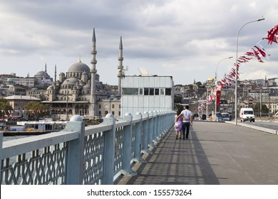 ISTANBUL - AUG 31 : A couple in love walking over Galata Bridge with New mosque in background on August 31, 2013, Istanbul, Turkey.