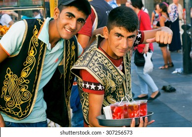 ISTANBUL - AUG 4: Two happy young vendors in the Turkish clothes selling drinks on the popular quay Eminonu on August 4, 2015 in Turkey. Istanbul is the world's fifth-most-popular tourist destination