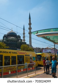 ISTANBUL, AUGUST 10, 2017 - local people waiting for the tram at Eminonu tram station with Yeni Cami (New Mosque) on the background