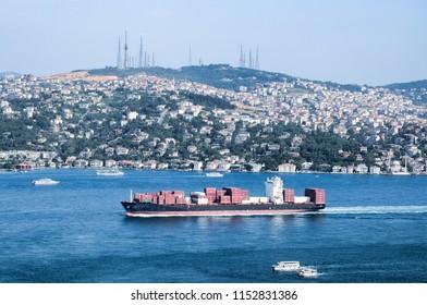 Istanbul Bosphorus Bridge, Turkey. Fully loaded container ship moving through.