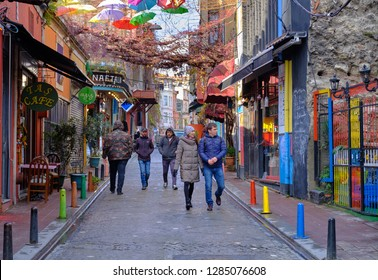 Istanbul - December 2018: Pedestrian walking down a street in colorful Balat area of Istanbul on a cold December day.
