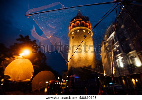 Istanbul, Galata Tower. View on architecture through a transparent umbrella in the rain. Nice bokeh. Tourism. Soft focus and slight noise of the atmosphere for lifestyle.