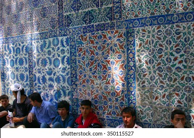 ISTANBUL - JUN 16, 2006 -  Iznik tile wall, young men  waiting for noon call to prayer [azan],	Eyup Mosque,	Istanbul	Turkey