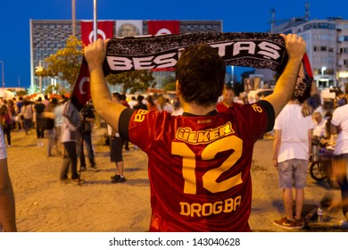 ISTANBUL - JUNE 19: Man with Galatasaray uniform lift up Besiktas scarf on June 19, 2013 in Istanbul, Turkey. Protests united opposing team supporters in Turkey.