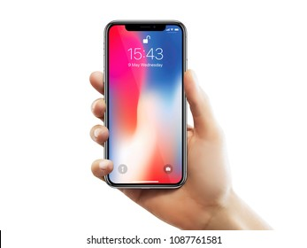 ISTANBUL - MAY 10, 2018: Apple iPhone X main screen holding by a female hand against isolated white background.