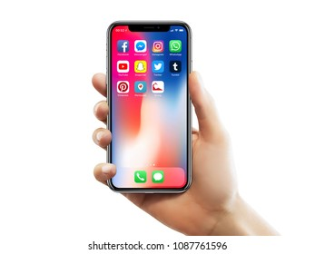 ISTANBUL - MAY 10, 2018: Apple iPhone X screen with well known social media app icons holding by a female hand against isolated white background.