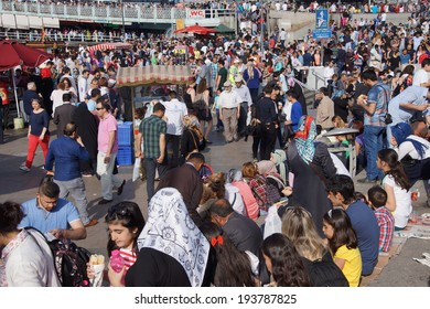ISTANBUL - MAY 18, 2014 - Crowds of tourists and locals buy snacks and head to the ferries in The Emininou area near Galalta bridge  in Istanbul, Turkey