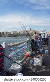 ISTANBUL - MAY 18, 2014 - Locals fish for sardines from the Galatya Bridge on the Golden Horn  in Istanbul, Turkey