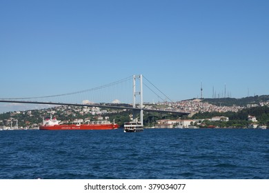 ISTANBUL - MAY 18, 2014 - Small boats and ferries pass under the  Bosphorus Bridge in Istanbul, Turkey