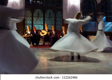 ISTANBUL - OCTOBER 21: Whirling dervishes and musicians perform to visitors in the event hall of Sirkeci Train Station, the old terminus of the Orient Express on October 21, 2005 in Istanbul, Turkey.