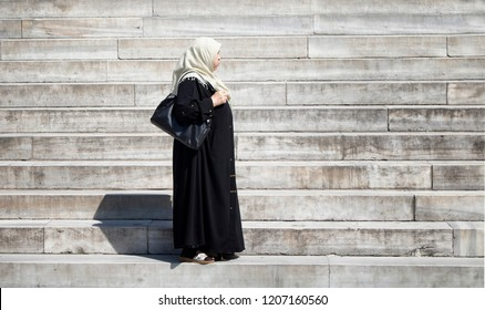 """ISTANBUL - SEPTEMBER 24, 2017: Middle age muslim woman wearing hijab standing on the stairs of historical mosque called """"Yeni Cami"""" in Istanbul."""