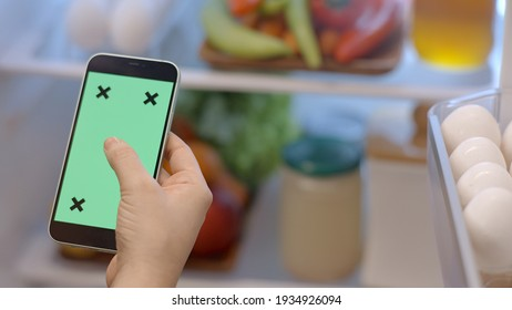 Istanbul, Turkey- 01.25.2021:Mobile phone with green screen tracking point with a refrigerator with vegetables and fruits in the background. On the phone, the woman scrolls and touches the screen.