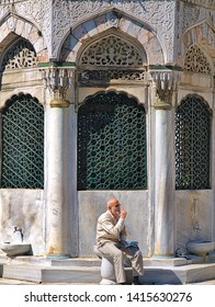 Istanbul, Turkey - 05/24/2010: Elder bearded bold man on marble seat, at Yeni Cami (new mosque) internal yard, in front of architectural construction with taps.