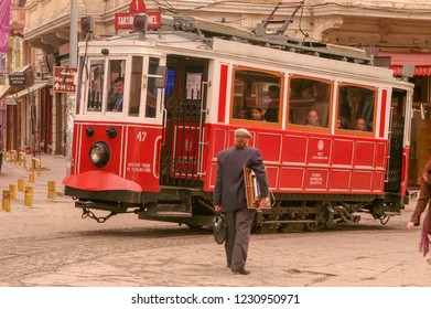 istanbul / turkey - 06 05 2018 in most famous street of istanbul; istiklal street, historic tram passing. A painter wtih works walking in front of tram