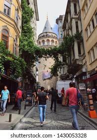 Istanbul / Turkey - 06/21/2018: Tourists walking toward famous Istanbul landmark Galata Tower in popular touristic district Beyoglu