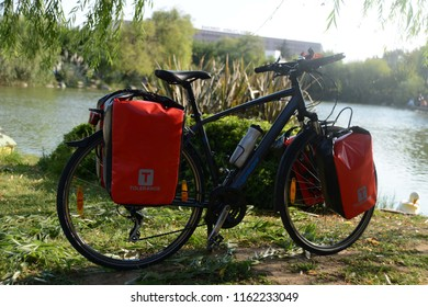 ISTANBUL, TURKEY - 19 August 2018 Loaded touring bicycle parking on the nature front of lake with red panniers at sunny day