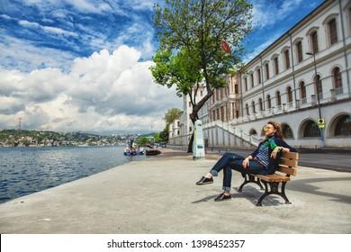 ISTANBUL, TURKEY, 2 May 2019: Girl sitting an embankment near Kuleli Military School, located on the Anatolian shore of Bosporus in Beykoz district of Istanbul.