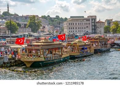 Istanbul, Turkey, 20 August 2018: Istanbul Restaurant terrace boats Golden Horn Galata bridge waterfront tower selling hot mackerel fish balik ekmek Eminonu