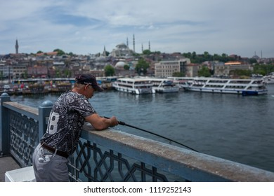 Istanbul, Turkey - 20 May, 2018: A fisherman waits for fishes to catch on Galata Koepruesue bridge.
