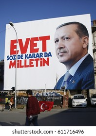 ISTANBUL, TURKEY, 30 MARCH 2017 A man walking with Turkish flag in front of huge Turkish President Recep Tayyip Erdogan's picture in Istanbul.