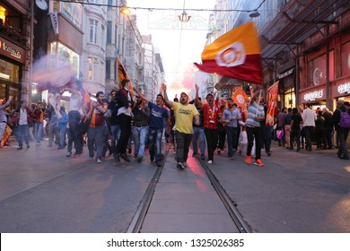 ISTANBUL / TURKEY - 30/05/2015: big crowd of Galatasaray S.K. football team fans marching with banners, flags, flares on Istiklal walking street, chanting, screaming, singing, celebrating a victory